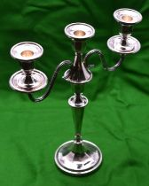 A silver candelabra with two arms and 3 removable sconces. Circular base, octagonal faceted base,