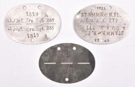 """Three Third Reich dog tags: aluminium, stamped """"1723 St Ammb/H.F.L. A.E.u.A.A.277"""", and """"1519 13/"""