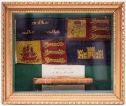 A gilt framed display of a Winston Churchill cigar and a car pennant from Churchill's car of the