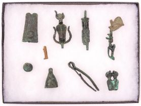 A glazed display case containing 10 small artifacts found at Karnak in 1900 by M. Le Grain, 26