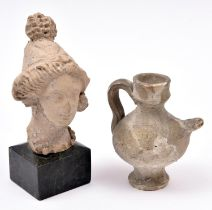 """An ancient Roman pottery head, 4¾"""" x 2¾"""" of a female, mounted on a square marble base; also a"""
