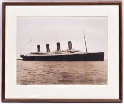A framed sepia black and white photograph of Titanic. Mounted within a wood cream carded frame