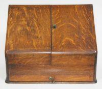 An oak fold out stationary box with calendar, length 39cm.