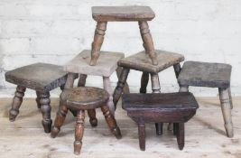 A group of seven wooden milking stools, heights ranging from 18cm to 26cm.