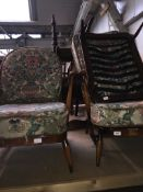 A pair of Ercol low armchairs with fleur de lys backs and an Ercol foot stool