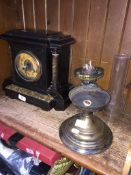 Ebonised wood clock and a brass oil lamp ( damaged ) with glass shade.