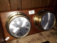 A brass cased clock and barometer mounted on a board