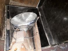 A metal box containing car headlight, axe and saw