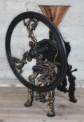 A large cast iron coffee grinder, height 60cm.