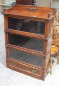 A three part mahogany sectional bookcase of shaped form with gallery, faux columns and lower drawer,