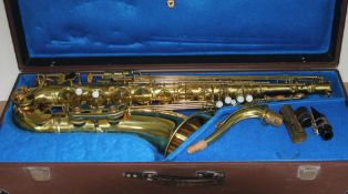 A brass tenor saxophone with hard case.