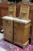 A pair of continental birds eye maple bedside cabinets, panelled backs with scroll carving and