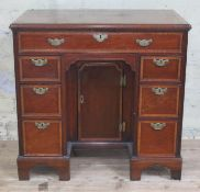 A George III mahogany knee hole desk, cross-banded top with moulded edge above one long and six