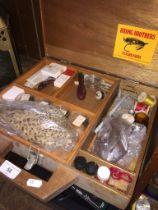A wooden box of fly fishing equipment, feathers, hooks, swivels, etc.