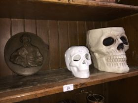 A resin Charles Dickens plaque, ceramic skull and a plastic skull bowl.