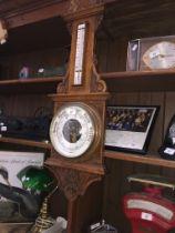 A carved oak cased barometer