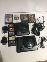 Box containing a Sega Megadrive and a Sega Megadrive II consoles and power cables. 2 Megadrive