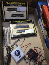 Box containing two Graham Farish model trains, Bachmann controller unit and a quantity of track.