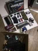 A large box containing scalextric track, accessories, racing trucks and a grand-prix set