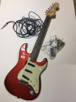 A stratocaster style guitar body in Candy Apple Red and neck. Pickups and pots etc have been removed