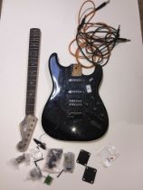 A black electric guitar in pieces. Stratocaster shape, pickguard has pots and pickups attached -