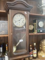 A wall clock with pendulum and key.