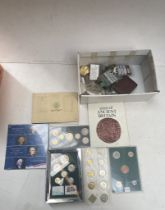 A box of world coin sets and a small box of collectables