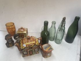 A box containing old bottles, skull figures and small collection of cottage ware.