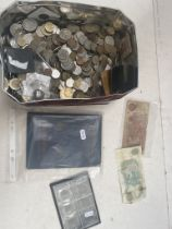 A tin of world coins and banknotes