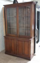 A mahogany cabinet bookcase, flared cornice top, glazed cabinet doors, the interior with