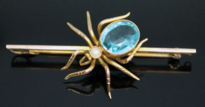 A novelty brooch modelled as a spider, millegrain set blue paste and a simulated pearl, marked '
