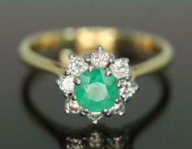 An emerald and diamond cluster ring, the central stone weighing approx. 0.50 carats, surrounded by