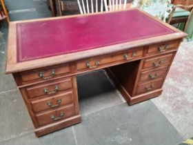 An oak pedestal desk circa 1900 with red leather top