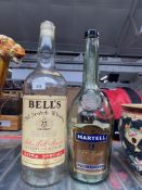 Two large glass bottles, one Bells whiskey and one Martell cognac.