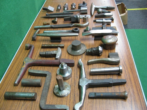 Quantity of approx forty heavy dollies and three hammer heads, mostly stored in oil soaked cling - Image 5 of 6