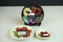 Three Moorcroft Pin Dishes, two in the Hibiscus pattern on white grounds and the other in the