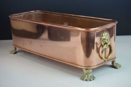 Copper Rectangular Planter with Brass Lion Mask Ring Handles and raised on four brass lion paw feet,