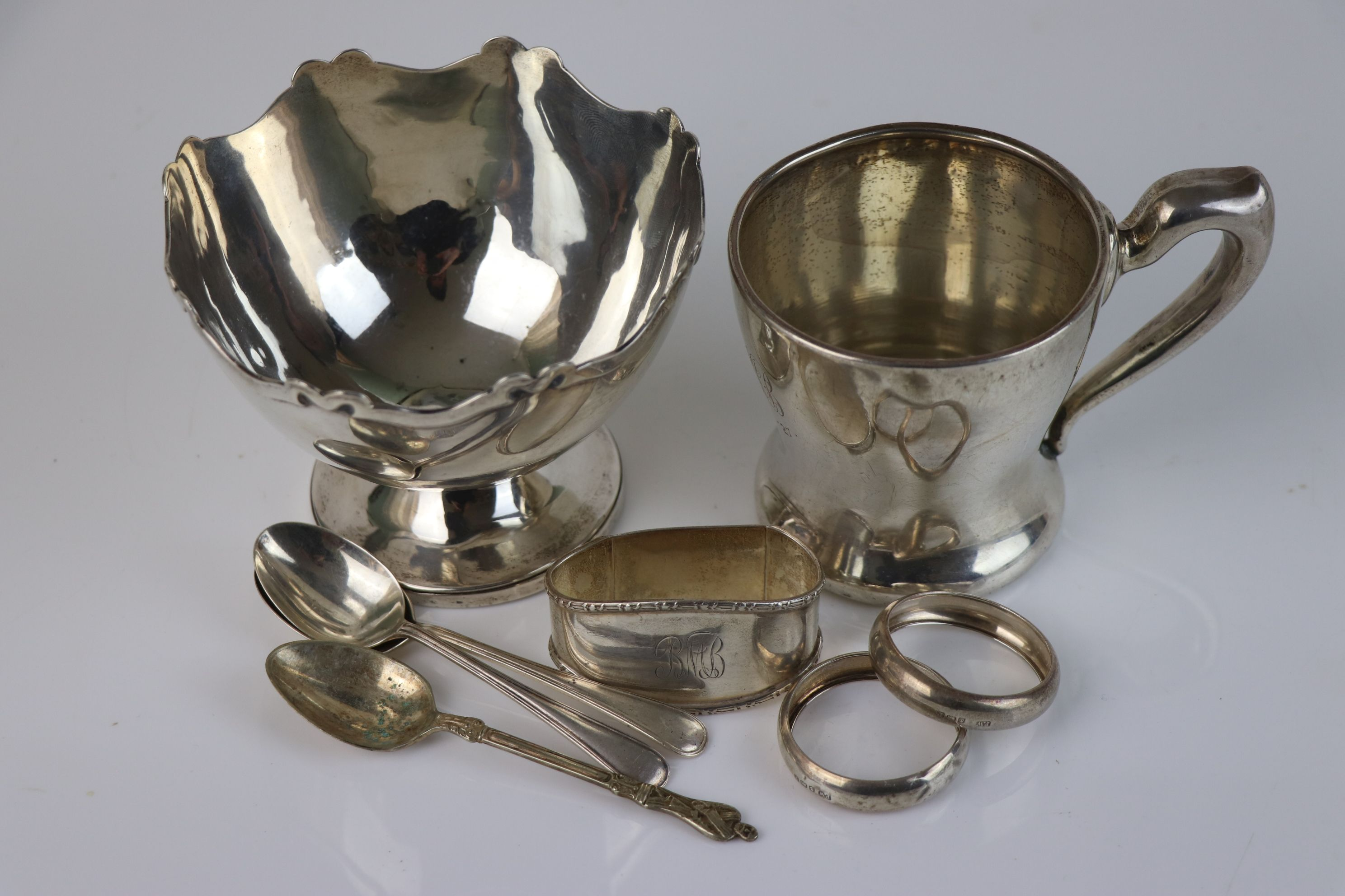 A collection of fully hallmarked sterling silver to include sugar bowl, cup, napkin rings and