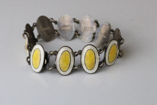 Early 20th century enamelled silver panel bracelet, eleven oval yellow and white enamelled panels,