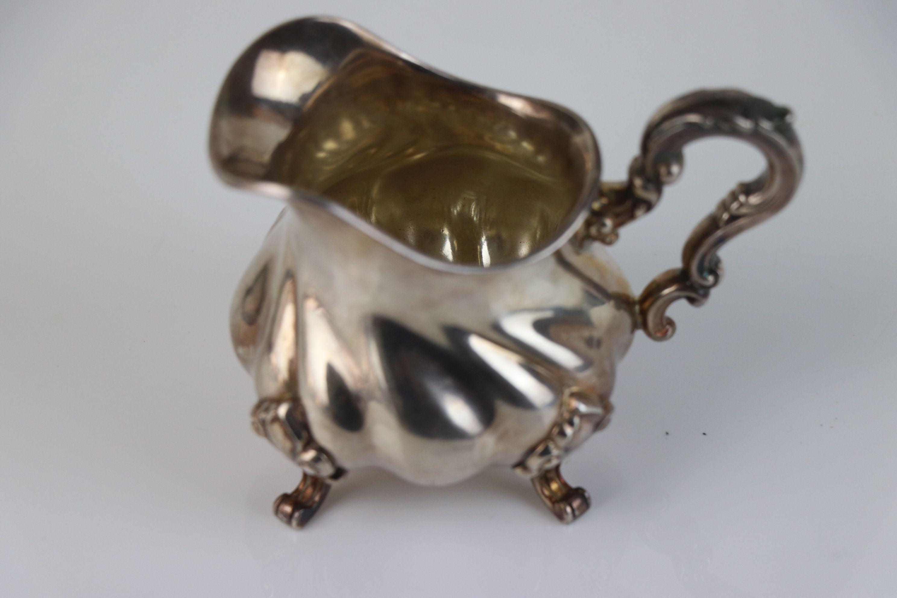 Silver cream jug raised on four scroll feet, bulbous body, acanthus leaf scroll handle, stamped