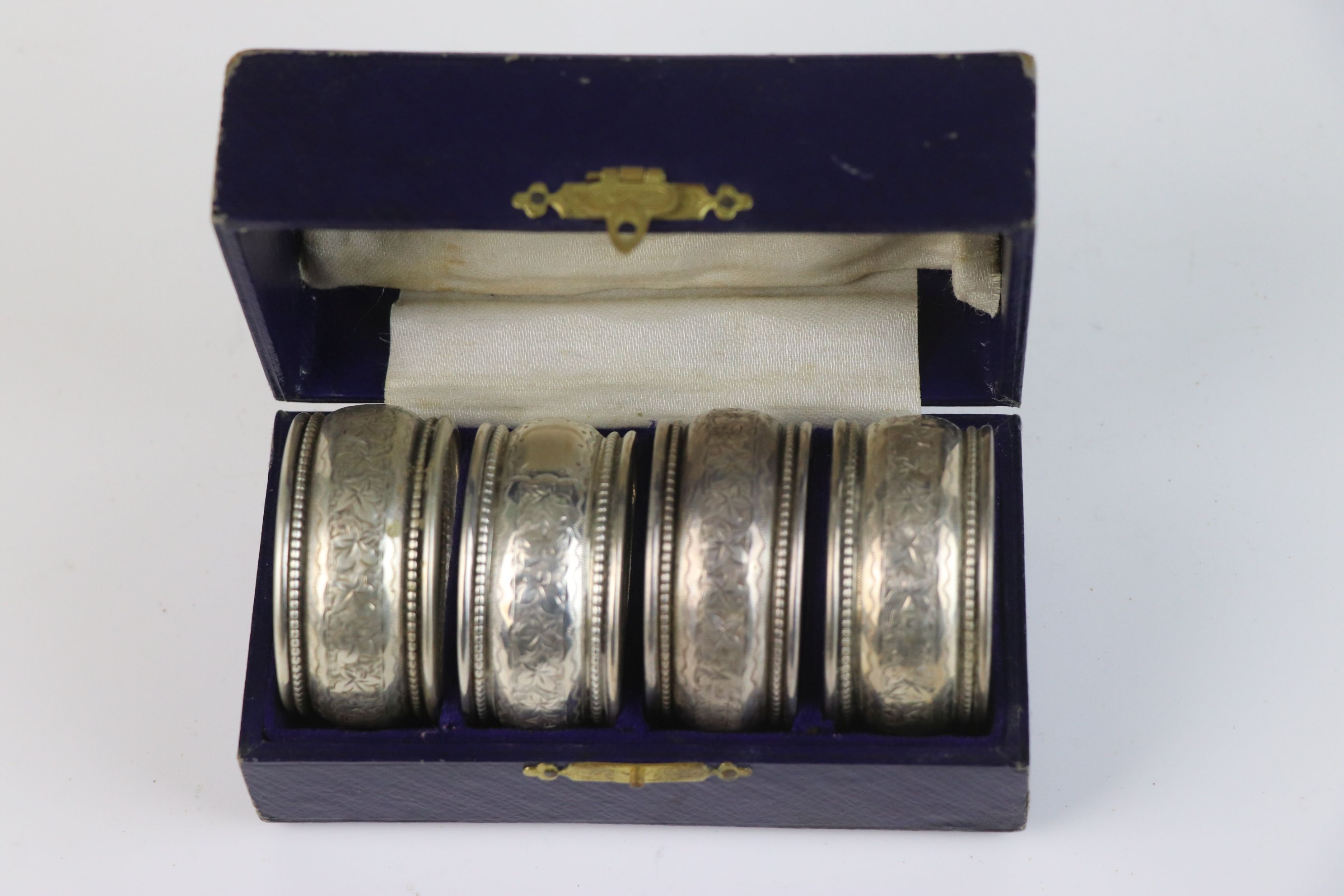 A fully hallmarked sterling silver cased set of four napkin rings, maker marked for William