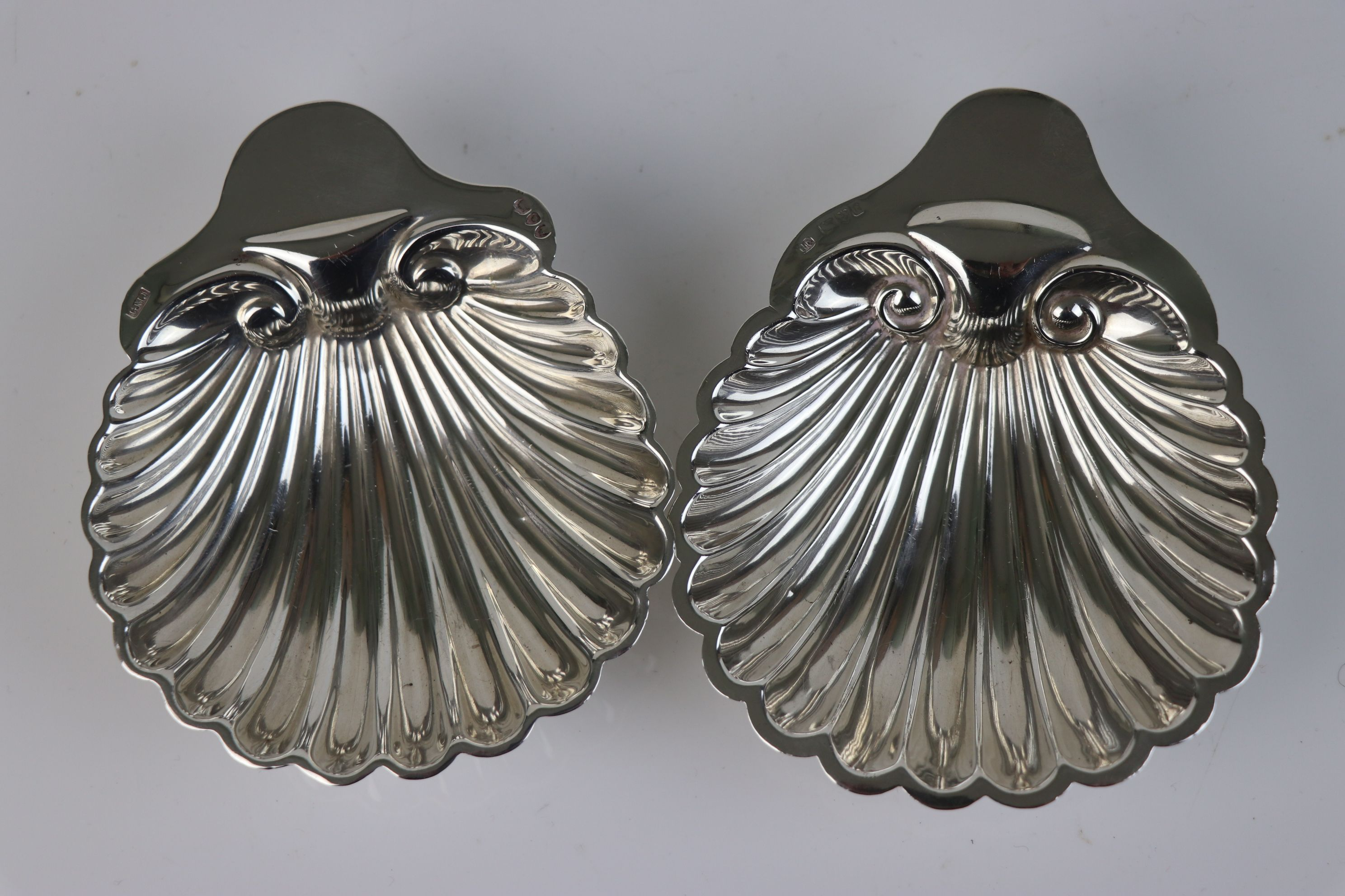 A pair of fully hallmarked sterling silver scalloped butter dishes, maker marked for Josiah Williams