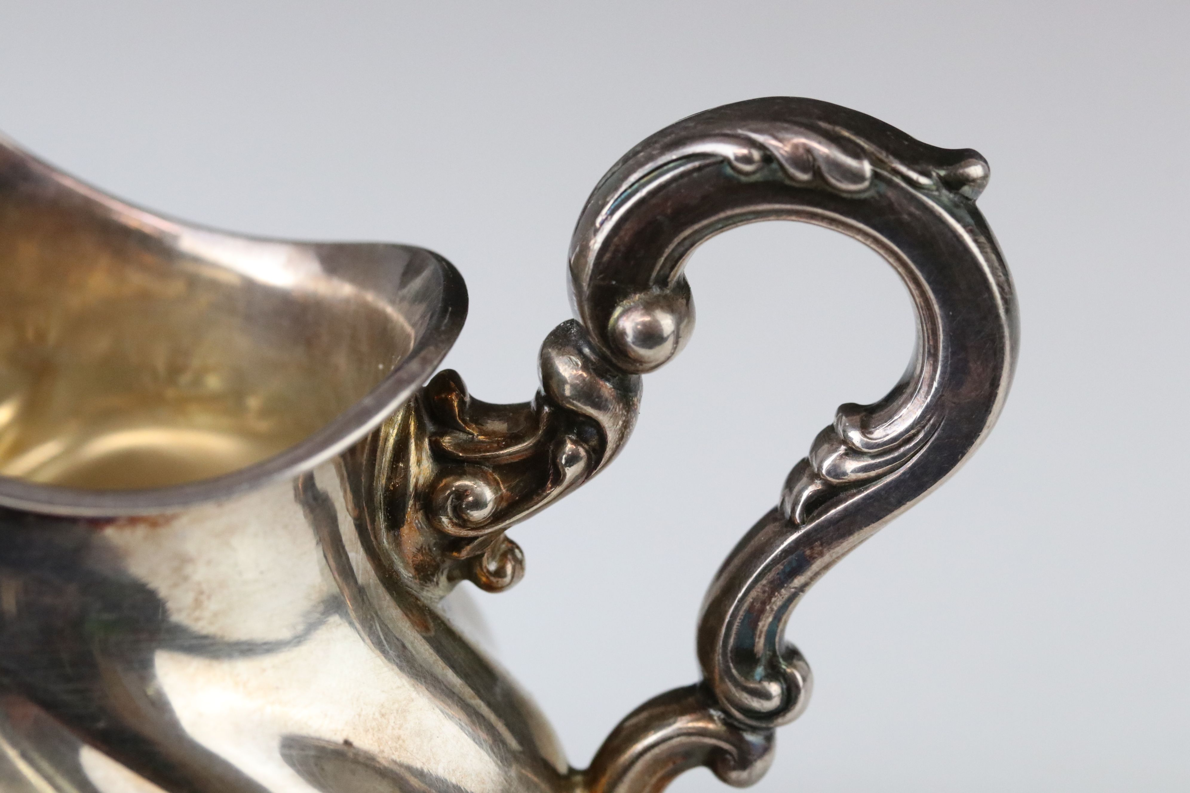 Silver cream jug raised on four scroll feet, bulbous body, acanthus leaf scroll handle, stamped - Image 6 of 9