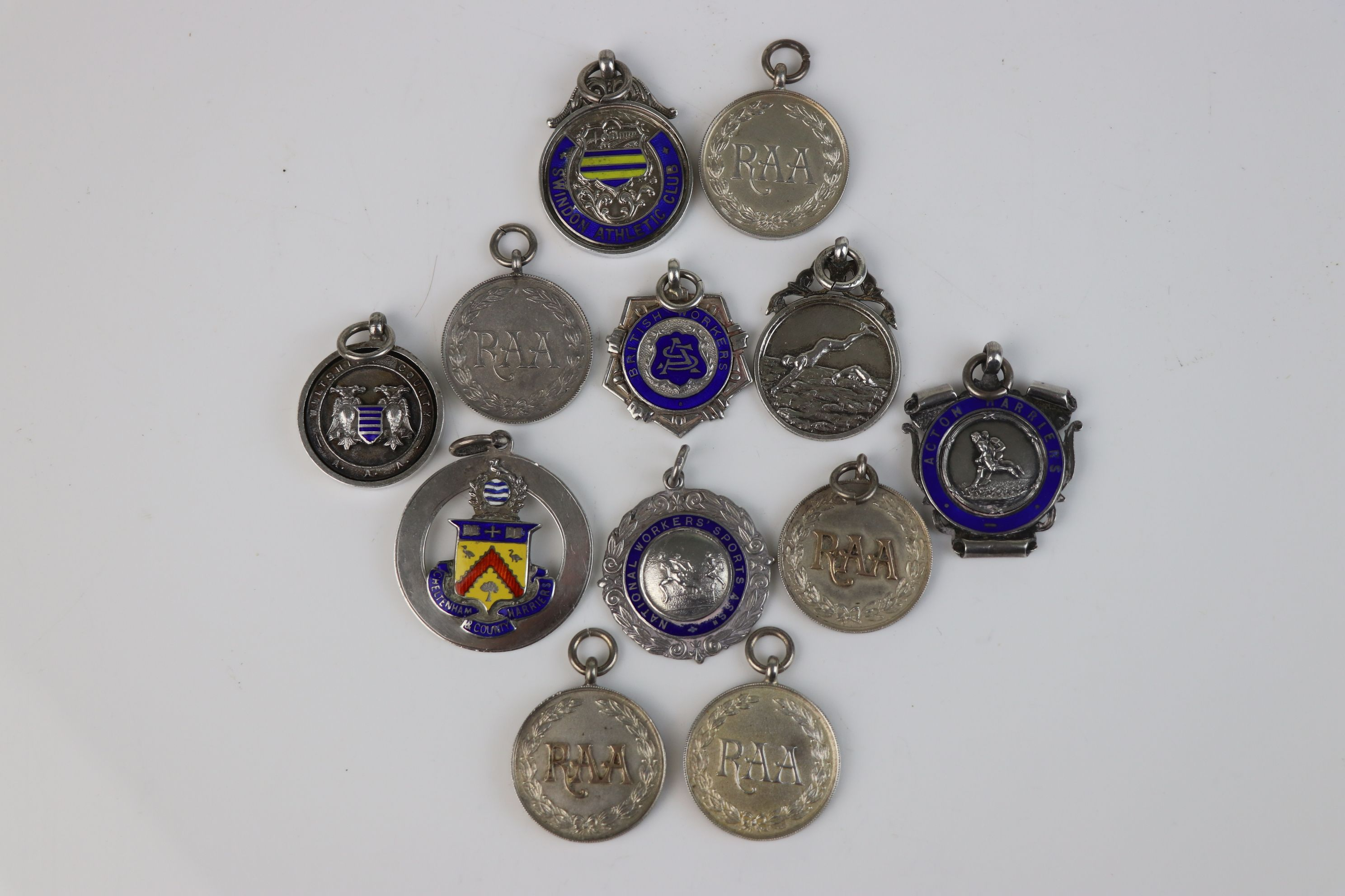 A collection of Twelve fully hallmarked sterling silver sports related watch fob medallions.