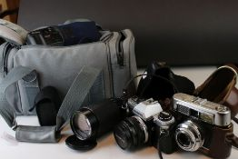 A collection of cameras and photographic equipment to include an Olympus OM10 35mm SLR camera.