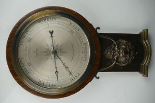 An early 20th century oak cased barometer with lion mask decoration.