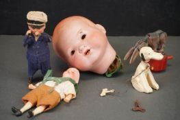A collection of antique toys to include a clockwork seaman and a German bisque dolls head.