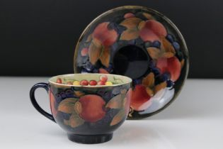 A Moorcroft Pottery cup and saucer with Pomegranate decoration, blue impressed mark and signature