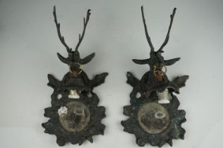 A pair of metal mirrored wall sconces with stag decoration.