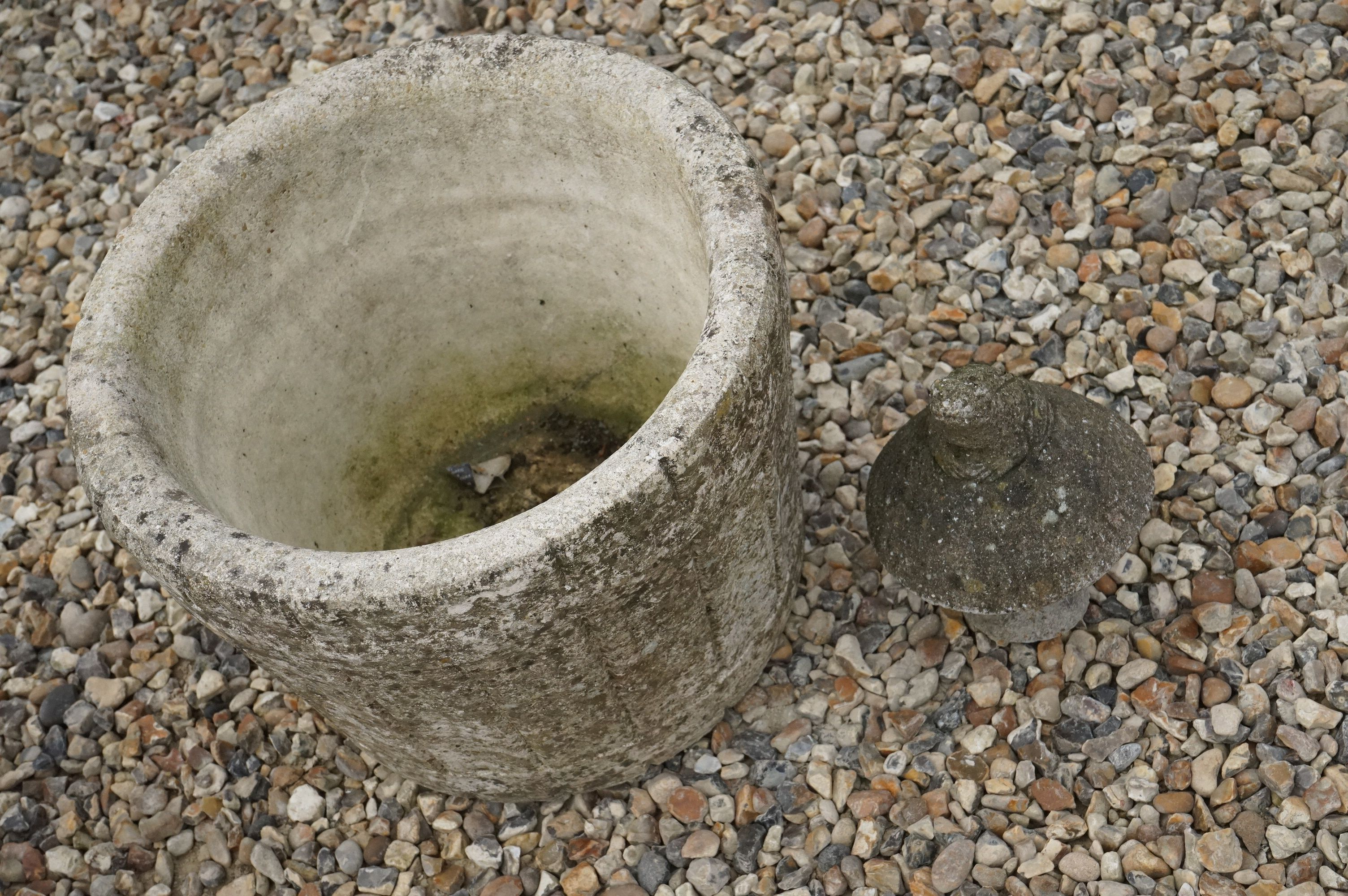A reconstituted stone planter in the form of a barrel.